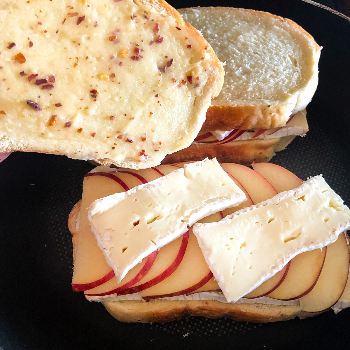 Layering thinly sliced brie and apples before grilling sandwich
