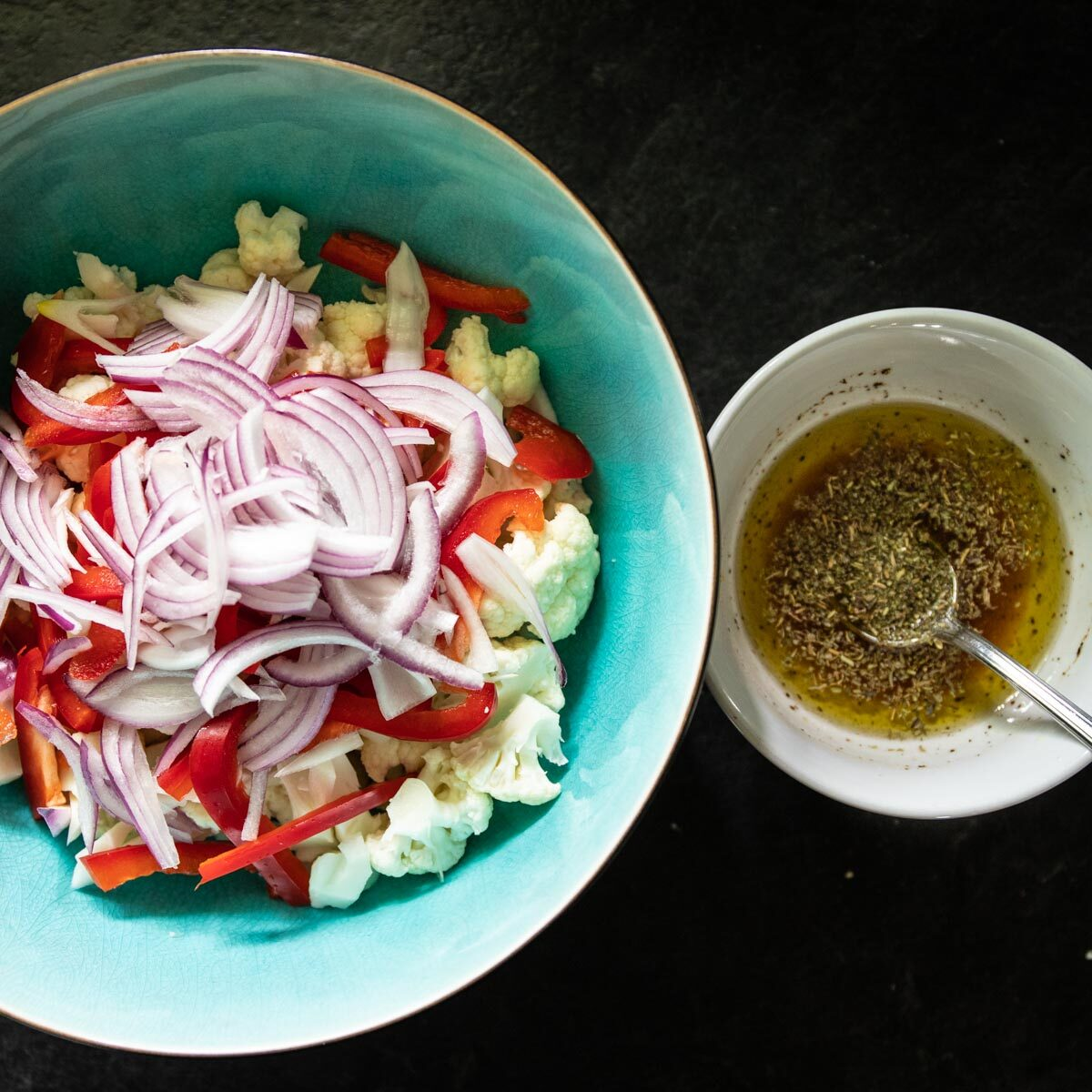 Cauliflower, Red Pepper and Red Onions Cut up in blue bowl for salad