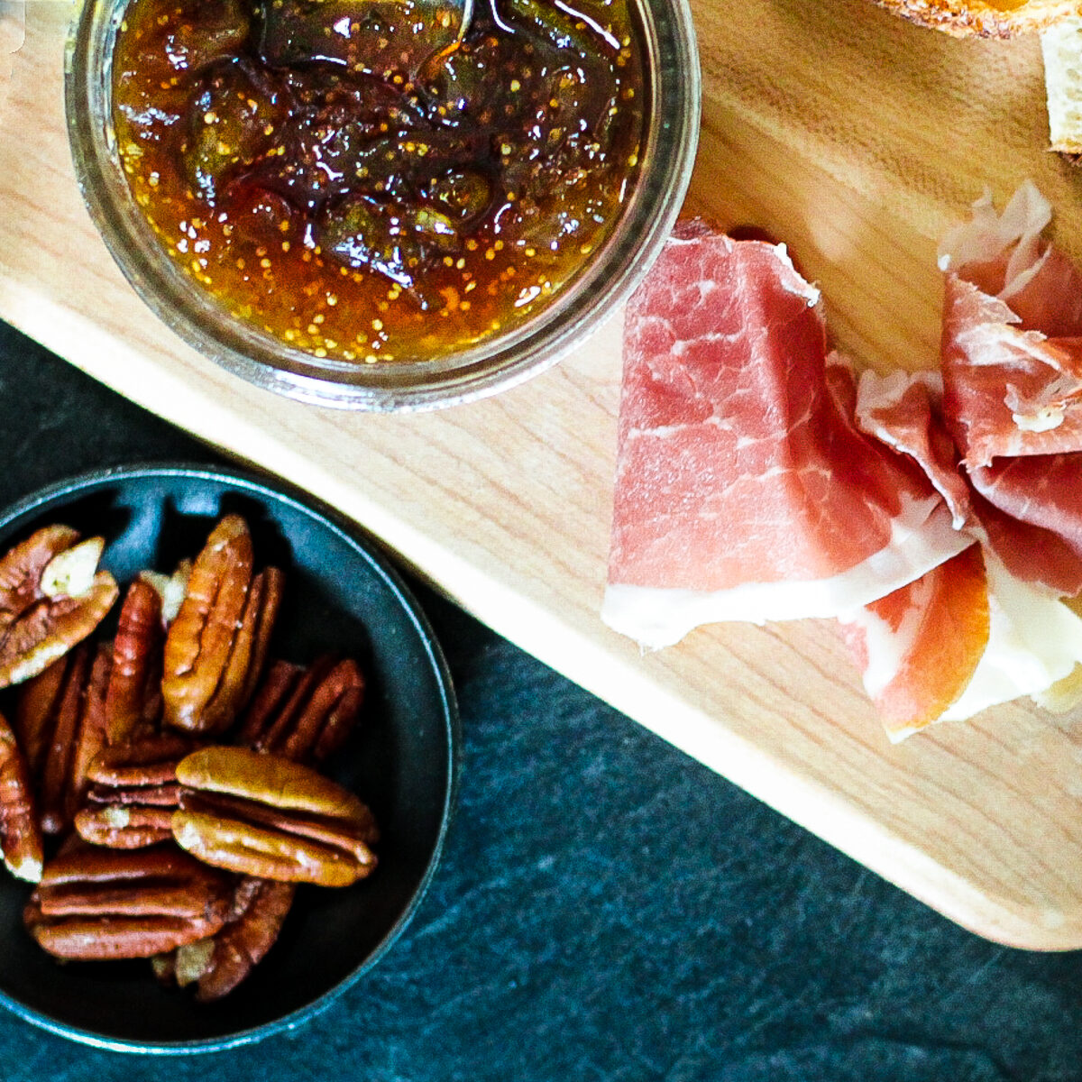 Fig jam in jar beside prosciutto and pecans