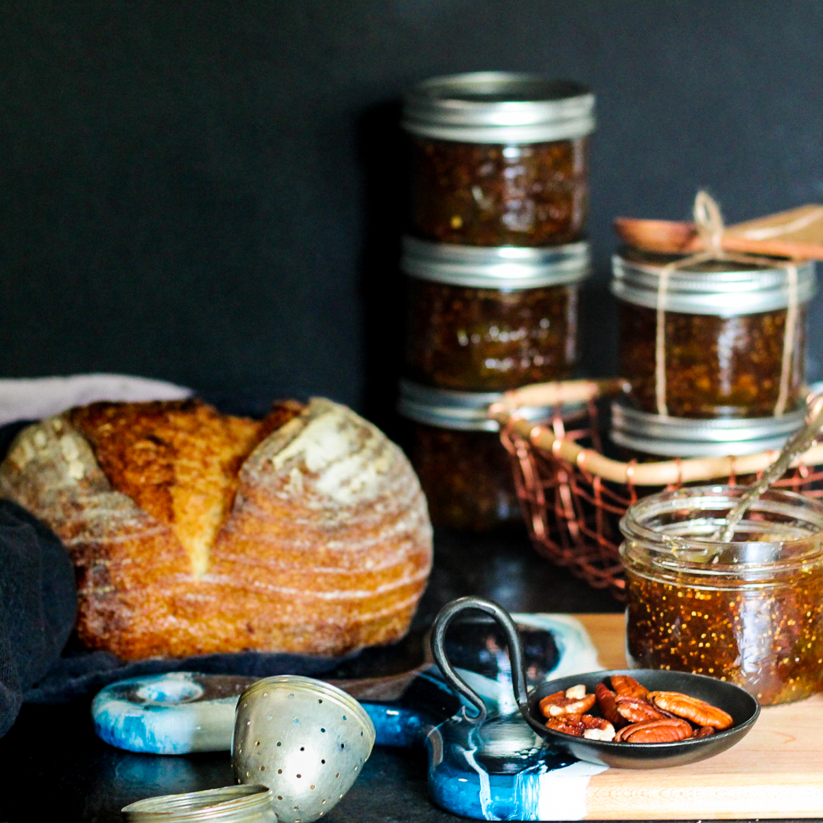 Jars of fig jam alongside a loaf of bread and pecans on a blue and brown charcuterie board