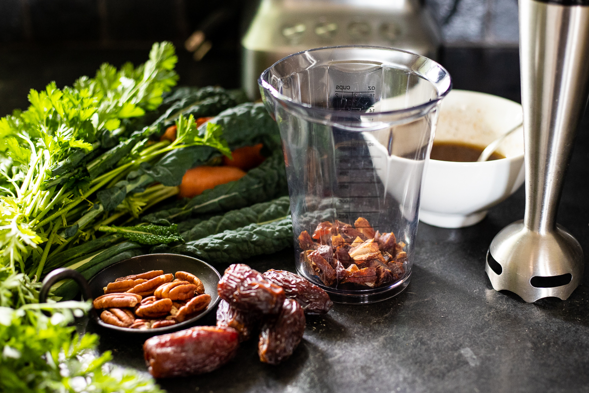 Ingredients including dates, oil, vinegar and nuts for the date and carrot salad with an immersion blender beside