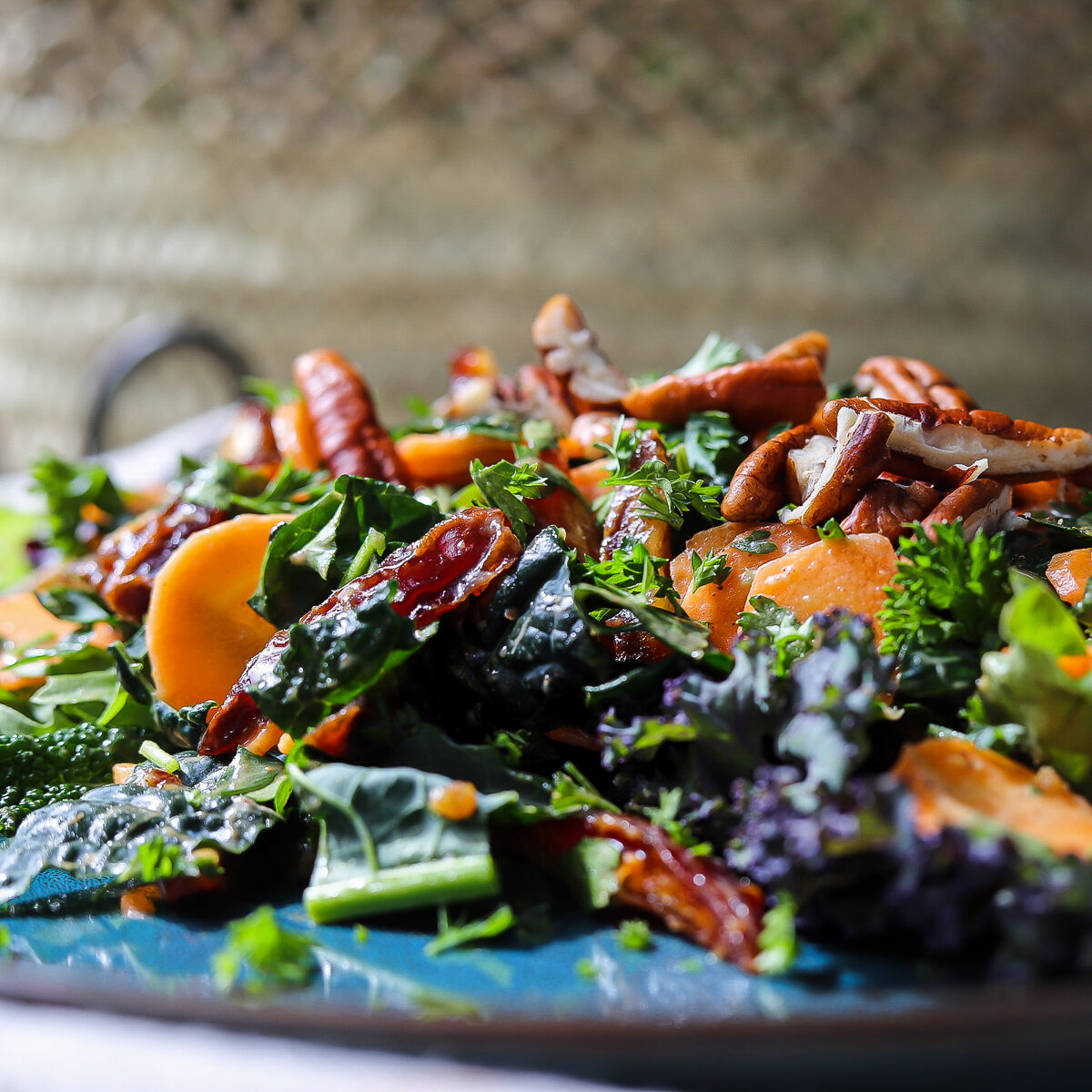 Date and carrot salad with kale on a blue plate