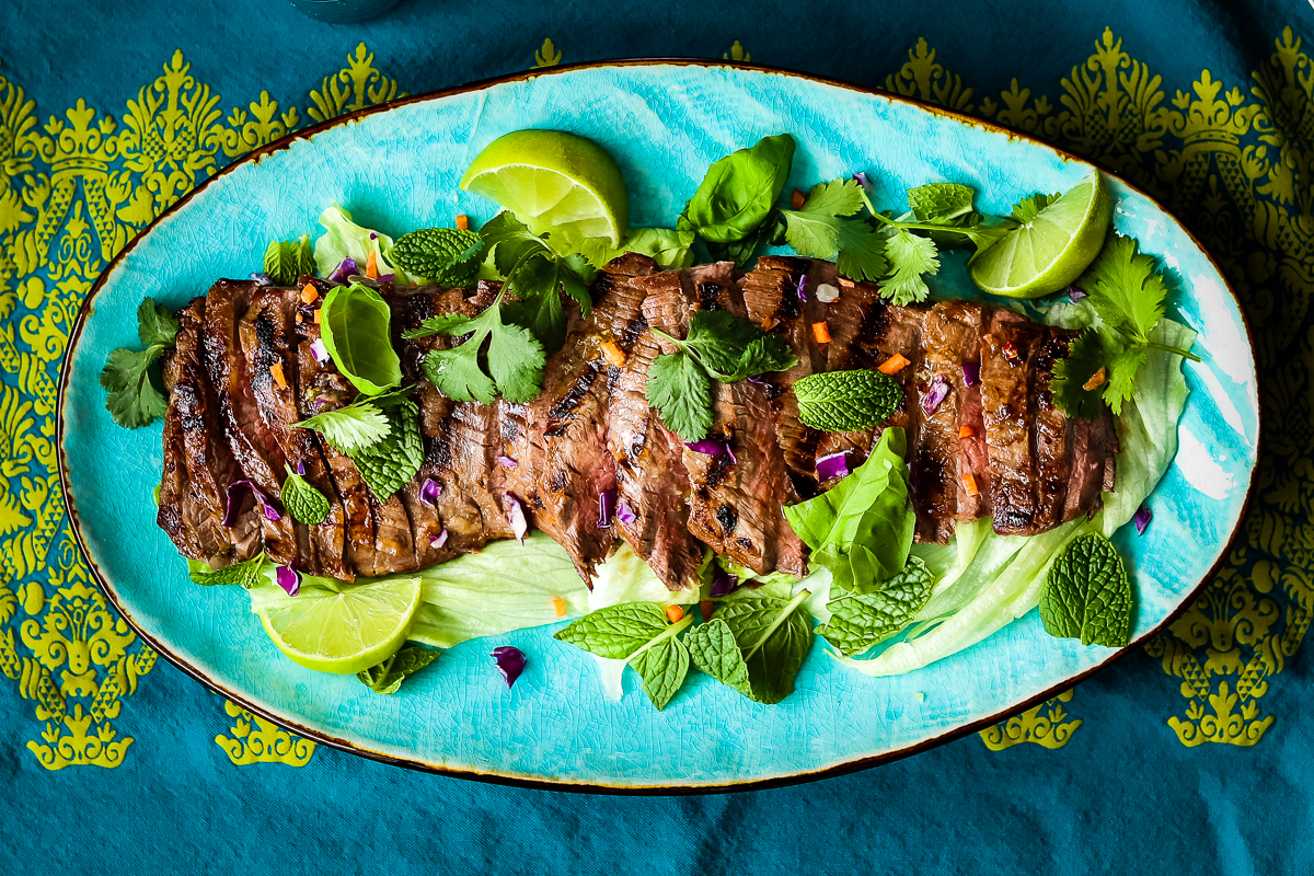 Flank steak salad with green herbs and lime wedges on a turquoise oval platter on patterned blue and green tablecloth