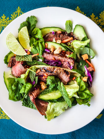 Flank Steak salad with Thai salad dressing in a white bowl set on a blue and green ornately patterned tablecloth