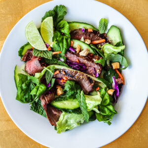 Sliced flank steak with greens and herbs in a white bowl on a gold charger